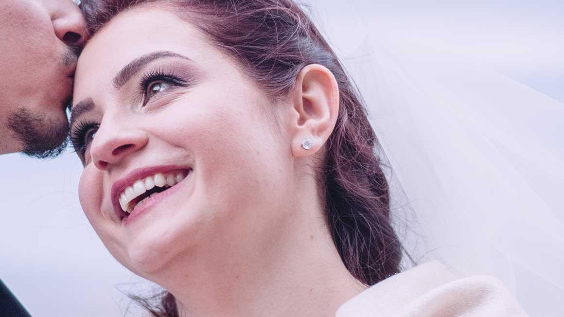 uśmiechnięta twarz kobiety ze zbliżeniem na makijaż, pocałunek w czoło