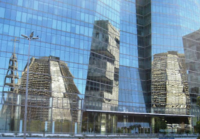 Distorted reflections of buildings in office block windows