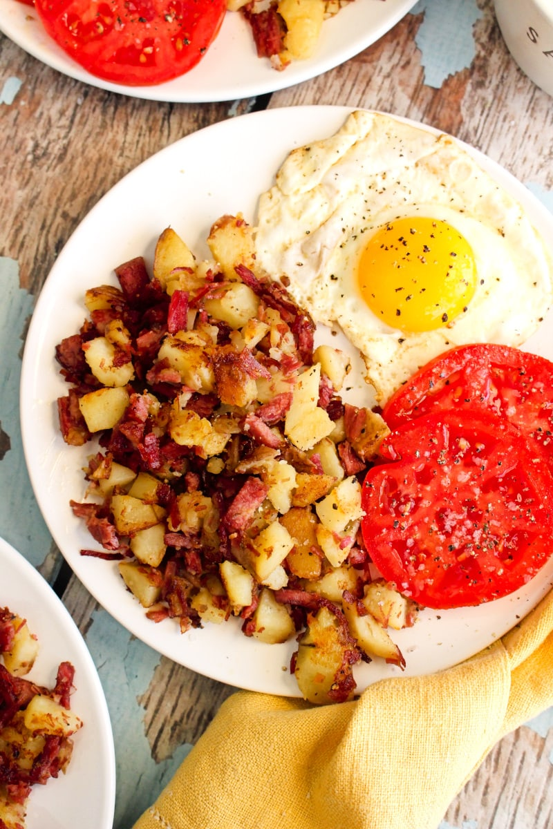 Top view of corned beef hash, a sunny side up egg, and sliced tomatoes on a white plate.