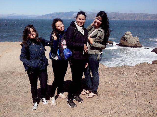 quatro mulheres posando para uma foto em frente ao mar