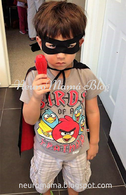 Masked 3 year old boy with a cape integración sensorial