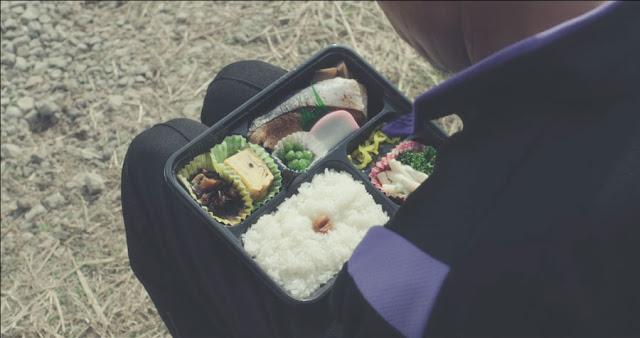 en las rodillas del protagonista reposa una caja de bento, vemos el arroz, tortilla, verduras, pescado, todo separado con blondas