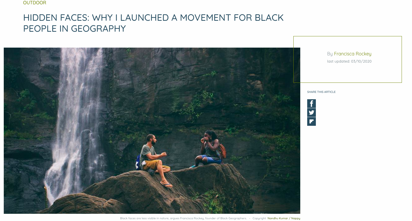 A Black man and woman sat on a cliffs in front of a waterfall