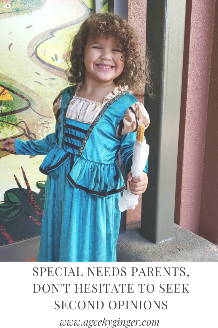A happy little girl with curly hair, wearing a teal and gold dress.