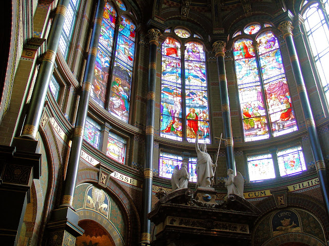 Close-up shot of the altar and the heavenly stained-glass windows that bathe the apse in colorful light.