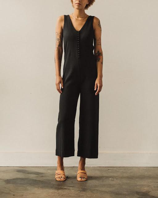 Model wearing a sleeveless black jumpsuit