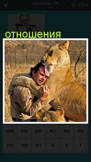 на поле сидят мужчина и лев в обнимку, хорошие отношения между ними