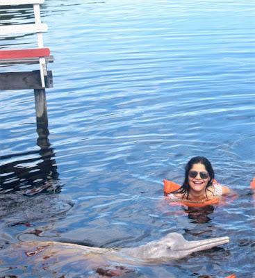 mulher nadando com o boto cor de rosa