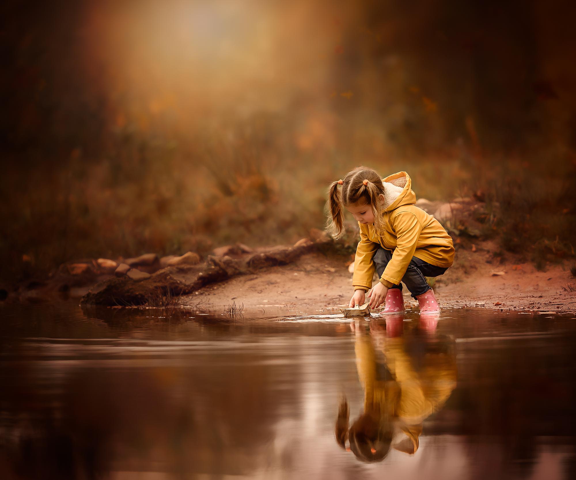Canon EOS R6 portret van een meisje met een papieren bootje bij het water met een gele regenjas van de Hema aan