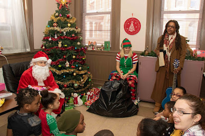 Children sing Christmas carols with Santa, his elf and Cassandra Harris Lockwoo.