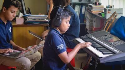 siswa bermain piano di kelas musik di sekolah internasional Yogyakarta, YIS