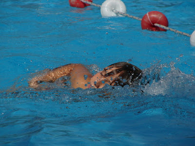 Image of a child in the pool learning how to swim freestyle.