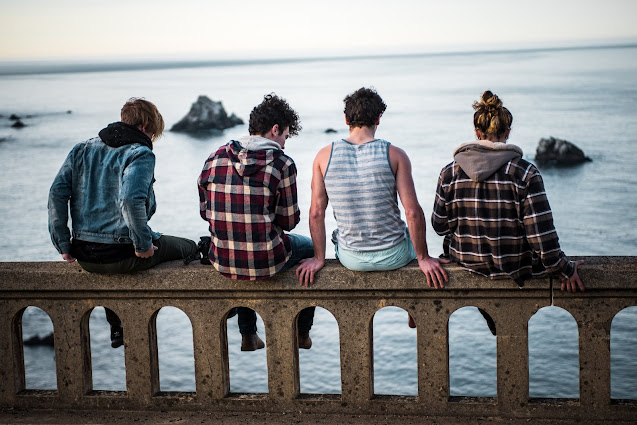 A picture with blue background of 4 friends sitting together on a bridge.
