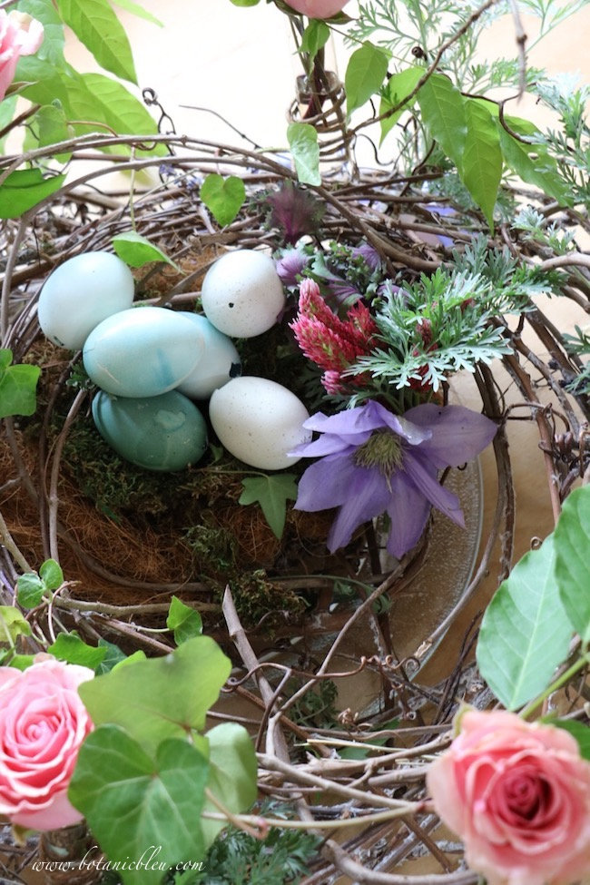 Beautiful Spring Centerpiece made using a large grapevine wreath, fresh roses, ivy, and colored eggs