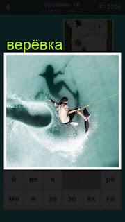 мужчина на доске на веревке катается по волнам 18 уровень 667 слов