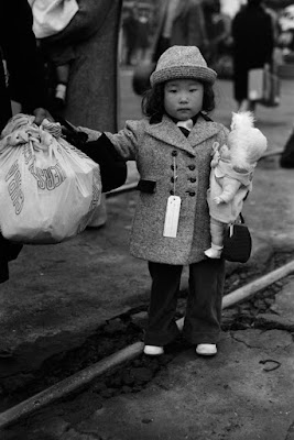 Child waiting to be taken to Manzanar, April 1942, Los Angeles, California. Photographer: Russell Lee. Library of Congress.