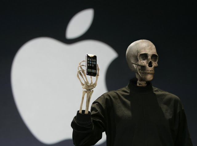 The skeleton of Steve Jobs stands on stage displaying the iPhone. He is dressed in an iconic black turtleneck.