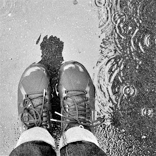 Photo looking down at walking shoes in a puddle in the rain