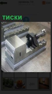 На поверхности стола стоят железные тиски в качестве инструмента