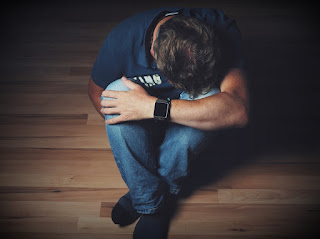 an image showing a man sitting on floor suffering from depression