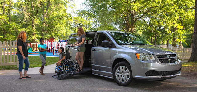 A silver minivan is in a disabled parking spot at a park. A woman is shown pushing a boy in a manual wheelchair. They are walking down a BraunAbility foldout ramp. A woman and a friend greet the two.