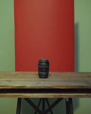 عدسة تصوير كانون 85 ملم سوداء ورائها خلفية حمراء
