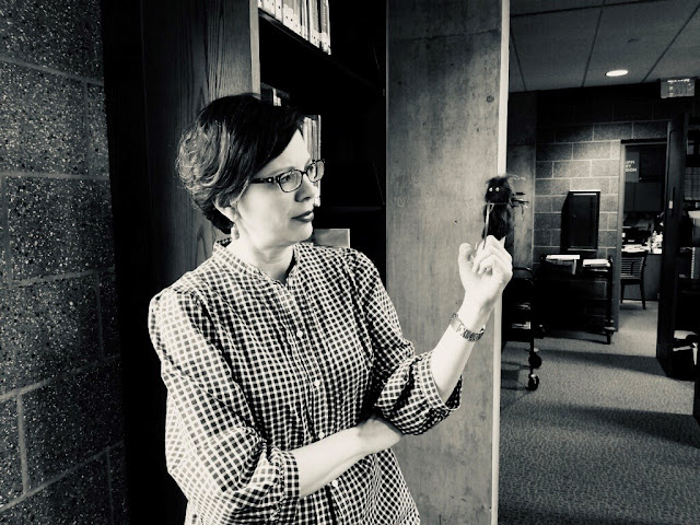 black and white photo of a woman wearing a checked shirt and glasses. She is staring intently of a fuzzy finger puppet on her index finger. Library shelves and carts are in the background.