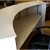 Why should one choose artificial material over wood to make reception desk?