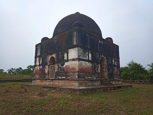 Discoloured domed square tomb structure in grassy area in Champaner