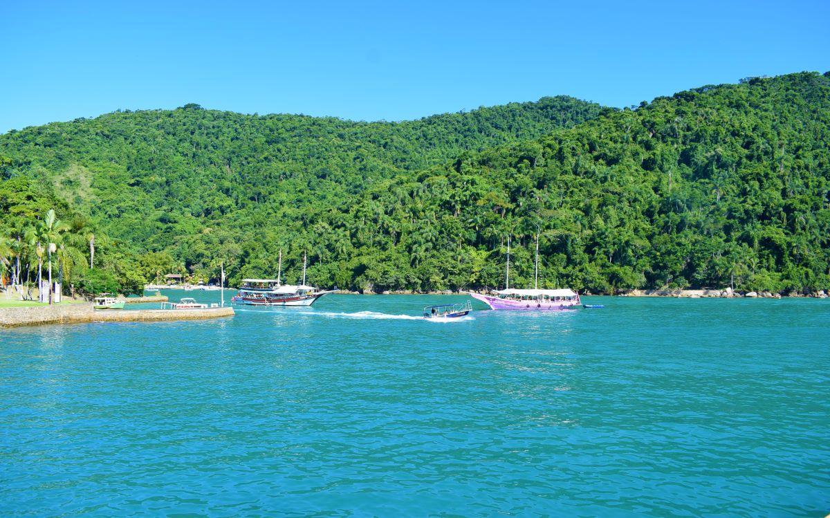 ilha pequena em mar aberto de águas esverdeadas e escunas ancoradas ao redor