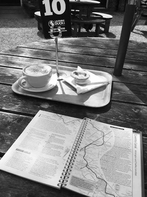 a wooden table at a cafe with coffee and cake on a tray and a guide book for the canals opened and ready for reading