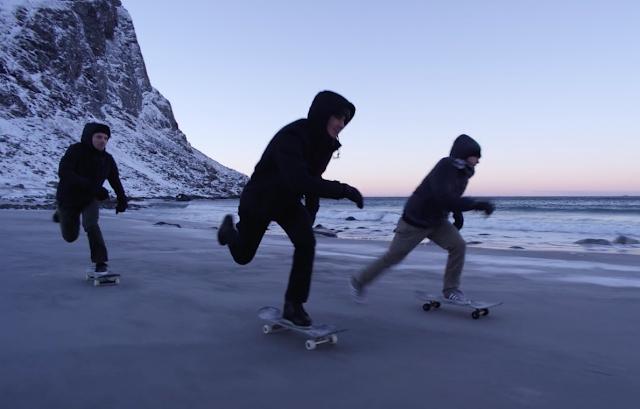 Drei junge Skateboarder fahren mit ihren Boards an einem norwegischen Strand auf den Lofoten entlang im Hintergrund sieht man Fjorde, Sand und Meer