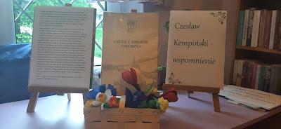 Na trzech sztalugach wystawka. Pierwsza sztaluga pokazuje kartkę na której znajduje się życiorys Czesława Kempińskiego. Druga sztaluga pokazuje książkę Czesława Kempińskiego Kartki z dziejów Jaworzna. Trzecia sztaluga prezentuje kartkę na której jest napis: Czesław Kempiński wspomnienie. Poniżej sztalug w żółtym wiklinowym koszyku umieszczone są różnokolorowe kwiaty z bibuły.