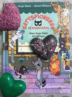 Bild på bokens omslag, bokens huvudkatt tittar på oss och håller en ansiktsmask bakom ryggen, gipshjärtan i olika färger ligger ovanpå boken.