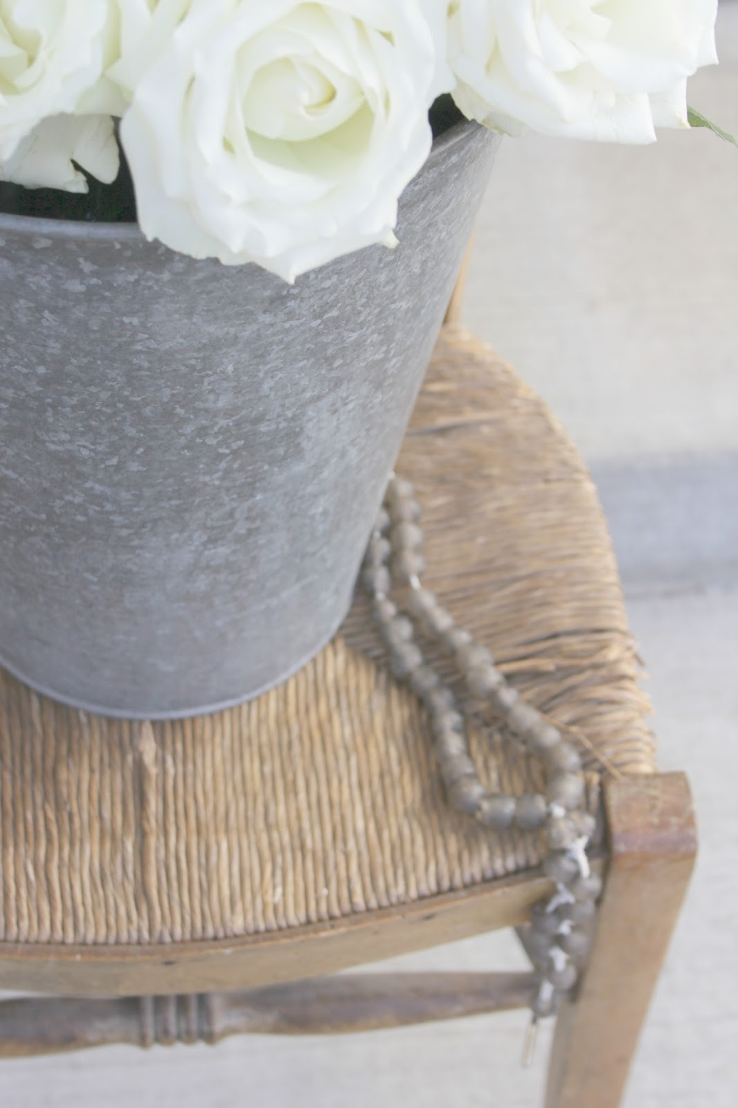 Galvanized bucket of roses on vintage French prayer chair by Hello Lovely Studio
