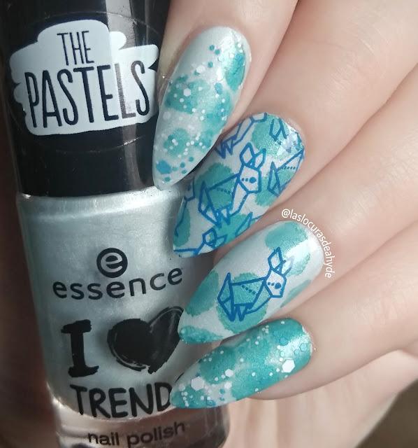 Nail art en tonos azules, base con efecto acuarela y topper en blanco ybazul. Conejos estampados en azul oscuro para Ostara