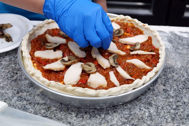 Anchor Food Professionals' Hot Cooking Chef, Chef Firuz scatters toppings on the Deep Cheese Pizza
