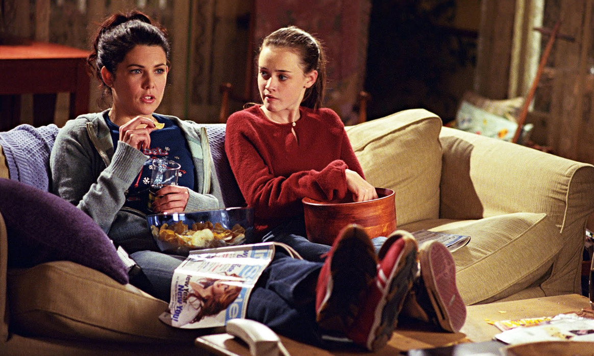 rory and lorelai sitting on the sofa eating pop corn watching a movie, gilmore girls revival, ravacholle belgium based lifestyle blog