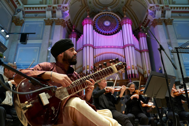 Sitarist and composer Jasdeep Singh Degun performing the world premiere of his sitar concerto with the Orchestra of Opera North, Huddersfield Town Hall, February 2020 (Photo Justin Slee)