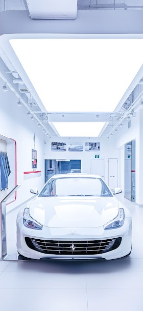 White Ferrari car inside white building wallpaper