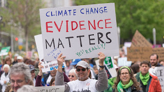 """Climate Change Evidence Matters"" sign at Science March (Credit: Albin Lohr-Jones/Pacific Press/LightRocket via Getty Images) Click to Enlarge."