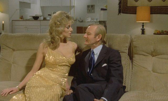 Julie Ege and Leslie Phillips sitting on a sofa