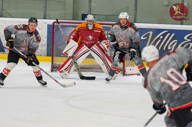 Hokeja vārtsargs pretinieku spēlētāju ielenkumā