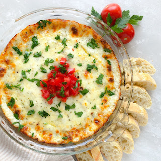 baked cheese dip garnished with tomatoes and parsley with bread on the side
