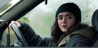 Kim (Maisie Williams) wearing a beanie hat driving a car