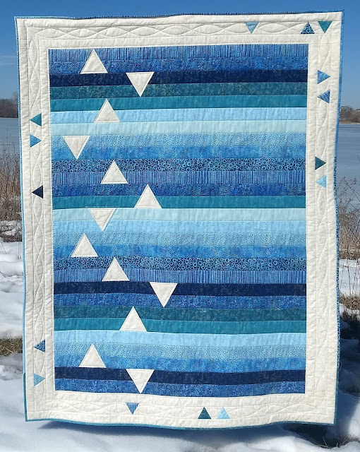 Quilt made with assorted blue and aqua strips, with inset cream triangles