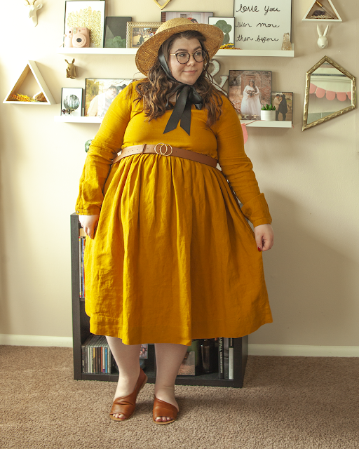 An outfit consisting of a brown panama hat, a mustard yellow long sleeve mock linen midi dress and brown d'orsay sandals.