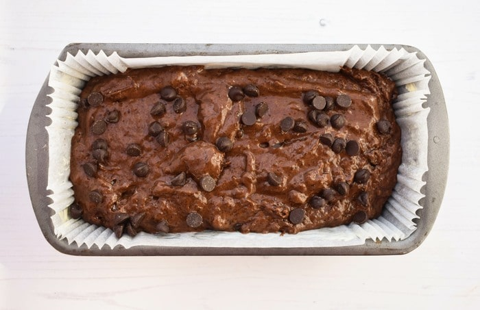 Chocolate cake batter in a lined loaf tin
