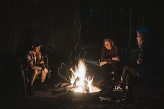 Jóvenes reunidos en torno a una hoguera.