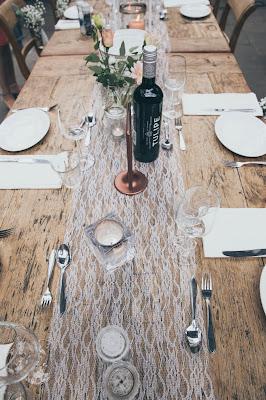 Mesa preparada para boda con una botella de vino encima